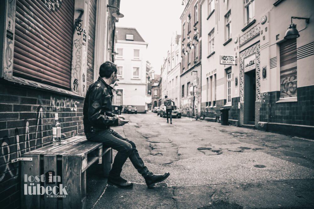 Clemensstrasse Lübeck Mann sitzt auf Palettenbank Graffiti, Lost in Lübeck