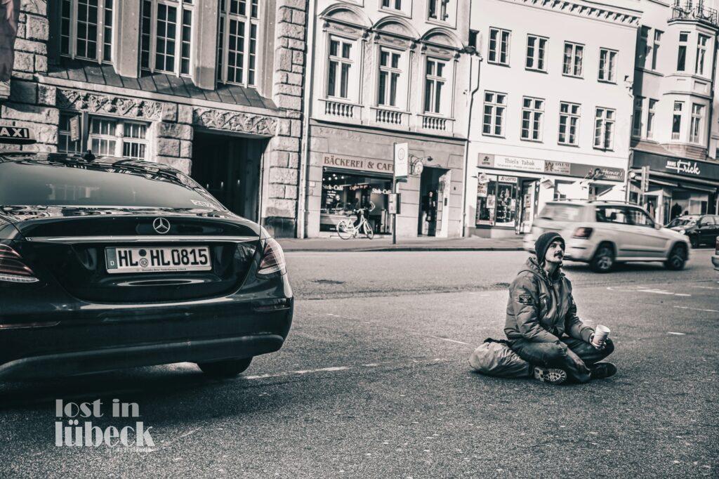 Beckergrube Lübeck Bettler vs. Mercedes Blick auf Bäckerei