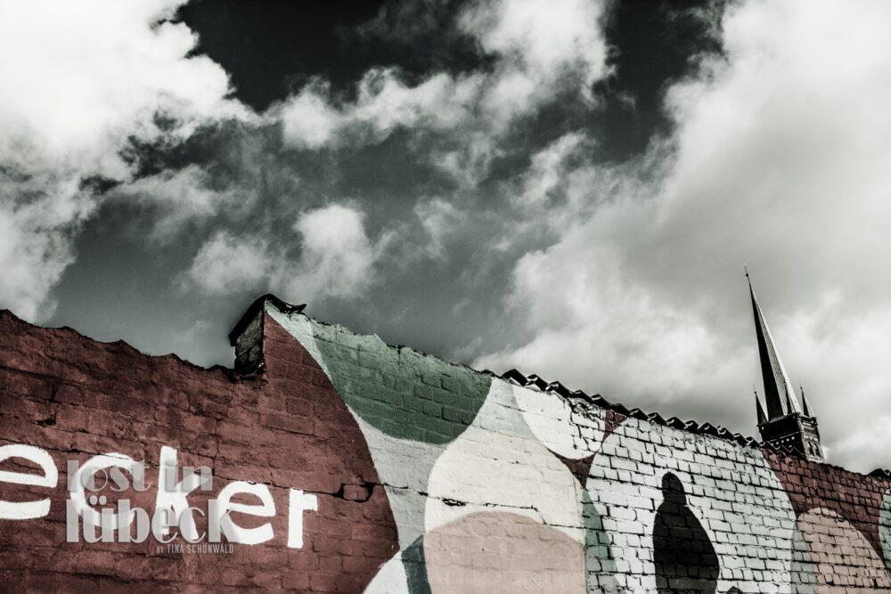Wallstrasse Lübeck Graffiti auf Mauer Kunsttankstelle Blick auf Kirchturm