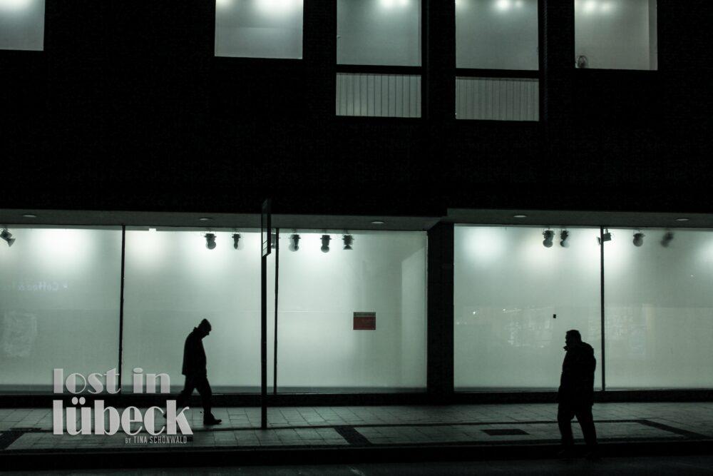 Mühlenstrasse Lübeck 2 Silhouetten vor leeren beleuchteten Schaufenstern