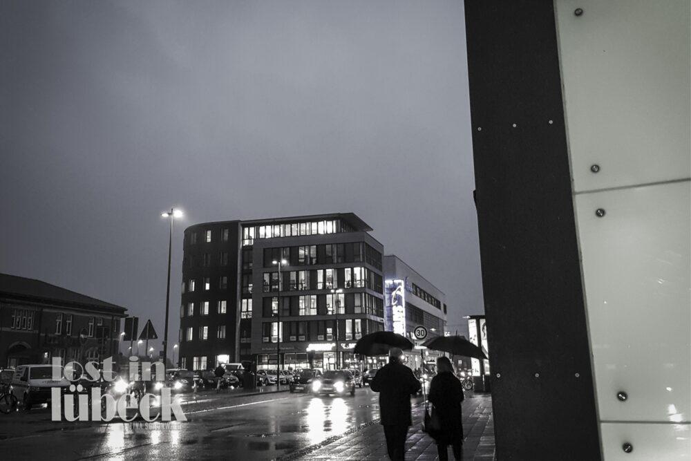 Am Bahnhof Lübeck Nachtblick auf beleuchtetes Saturngebäude